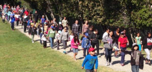Families and school staff hiking together on a community field trip.