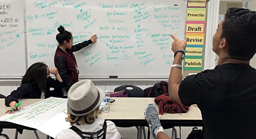 Young female student pointing at white board with a student and teacher looking on.