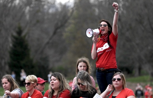 Kentucky teachers protest at the state capitol. A teacher in a read t-shirt holds her fist in the air and speaks into a megaphone.