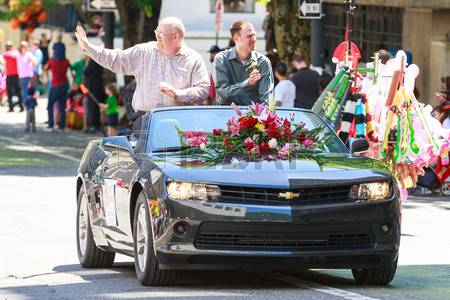 Brett Bigham and husband riding in the Rose Festival Parade in Portland, Oregon on the back of a convertible.